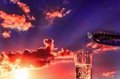 Strömendes Getränk bei Sonnenuntergang Stockbilder