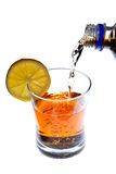 Strömendes Getränk in ein Glas mit Zitronescheibe Stockbilder