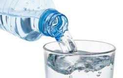 Strömendes Glas Wasser von einer Plastikflasche lokalisiert lizenzfreies stockbild