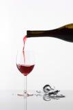 Strömendes Glas Wein auf Weiß Stockfotografie