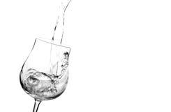 Strömendes Wasser in das Glas getrennt auf Weiß Stockfotografie