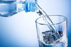 Strömendes Wasser der Nahaufnahme von der Flasche in Glas auf blauem backgrou Stockfotos