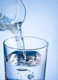 Strömendes Wasser der Nahaufnahme von einem Krug in Glas auf einem blauen backgroun Lizenzfreie Stockfotos