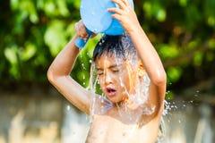 Strömendes Wasser des Jungen auf seinem Kopf Stockfotografie