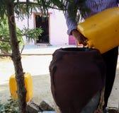 Strömendes Wasser des Mannes von der Dose in ein Glas lizenzfreies stockfoto