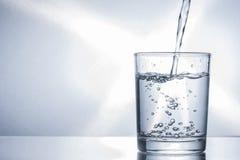 Strömendes Wasser in ein Glas lizenzfreies stockbild