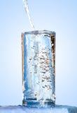 Strömendes Wasser in ein Glas Lizenzfreie Stockfotos