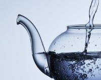 Strömendes Wasser in eine Teekanne Stockfotografie