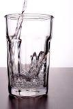 Strömendes Wasser in Glas Stockbild