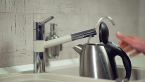 Strömendes Wasser vom Hahn in einen Wasserkocher stock video footage
