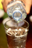 Strömendes Wasser von der Flasche Stockbild