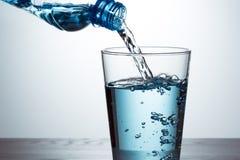 Strömendes Wasser von der Flasche in Glas stockfotografie