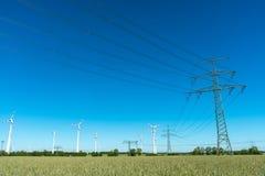 Strömförsörjninglinjer och vindturbiner Arkivfoton