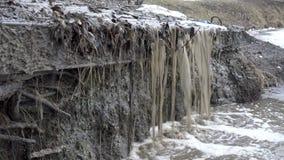 Strömmen av smutsiga leriga vattenflöden ner från en ström en vattenfall i floden på våren smältande snow lager videofilmer