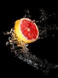Strömmen av vatten och grapefrukten Royaltyfri Bild