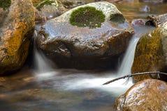 Strömmen av vatten som kör vaggar igenom royaltyfri fotografi