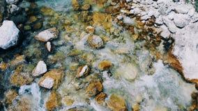 Strömmen flödar mellan de steniga bankerna Vatten flödar över stenen arkivfilmer
