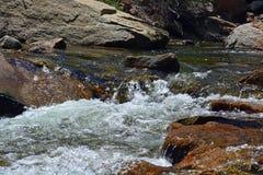 Strömvattenflöden förbi stort vaggar Arkivfoto