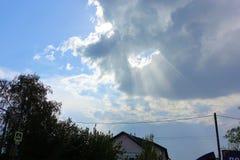 Str?larna f?r sol` s tr?nger igenom molnen i himlen royaltyfri fotografi