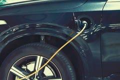 Str?mf?rs?rjningen f?r uppladdning av en elbil laddande elkraft f?r bil arkivbilder
