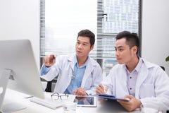 Str?vsamma doktorer som granskar patients mapp arkivfoto