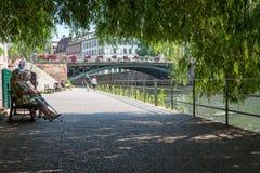 Straßburg, Frankreich - 11. August 2015: Ältere Menschen, die auf einer Bank, stehend im Schatten, auf Sommer sitzen still Lizenzfreie Stockfotos