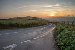 Straße über Hügeln bei Sonnenaufgang Stockbilder
