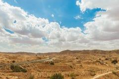 Straße überschreitet durch felsige Sahara-Wüste, Tunesien Lizenzfreie Stockfotos