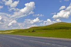 Straße auf dem Gebiet, Langstreckenspur auf dem Gebiet Schöne grüne Hügel Blauer Himmel mit flaumigen Wolken Lizenzfreie Stockfotos