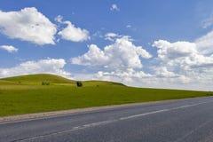Straße auf dem Gebiet, Langstreckenspur auf dem Gebiet Schöne grüne Hügel Blauer Himmel mit flaumigen Wolken Lizenzfreies Stockbild