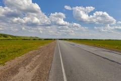 Straße auf dem Gebiet, Langstreckenspur auf dem Gebiet Schöne grüne Hügel Blauer Himmel mit flaumigen Wolken Stockfoto