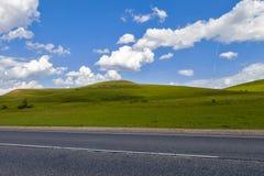 Straße auf dem Gebiet, Langstreckenspur auf dem Gebiet Schöne grüne Hügel Blauer Himmel mit flaumigen Wolken Stockfotos