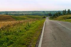 Straße auf den Gebieten, der endlose Weg von Abfällen und Aufstiege in der Straße, ein weiter Weg in der Reise Stockfoto