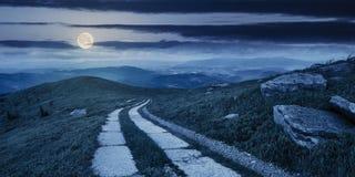 Straße auf einem Abhang nahe Bergspitze nachts Stockbilder