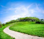 Straße auf einem grünen Hügel Stockbild