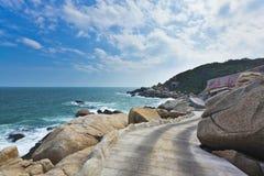 Straße auf Insel mit großem Stein Stockfotografie