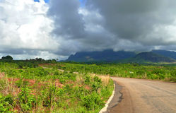 Straße in den Bergen. Der bewölkte Himmel. Afrika, Mosambik. Lizenzfreies Stockfoto