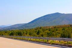 Straße in den Bergen an einem sonnigen Tag lizenzfreie stockfotografie