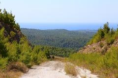 Straße in den grünen Hügeln von Sithonia in Griechenland Im Hintergrund die Horizontlinie des Ozeans und des Himmels Lizenzfreie Stockbilder