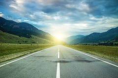Straße in den Sommerbergen zum Sonnenuntergang Lizenzfreies Stockfoto