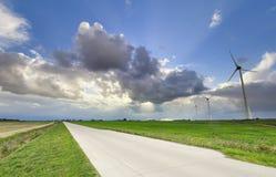 Straße in der Landschaft mit schönem Himmel und Turbinen stockfotos