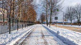 Straße in der Stadt im Winter, gesäuberter Schnee säuberte die Straße vom Schnee im Park Stockbild