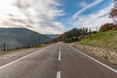 Straße des europäischen Landes , Biegen Verkehrsschild, Bäume und heller blauer Himmel nach rechts ab Asphalt und trockenes Gras Lizenzfreies Stockfoto