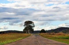 Straße des offenen Landes voran mit Wolken u. Feldern Lizenzfreie Stockfotos