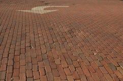 Straße des roten Backsteins mit Weiß gemaltem Pfeil Lizenzfreies Stockfoto