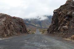 Straße, die in Abstand Berge durchläuft stockbild
