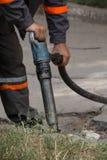 Straße, die Arbeiten mit Jackhammer repariert Stockfotos