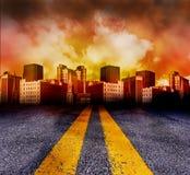 Straße, die in die Stadt mit rotem Sonnenuntergang einsteigt Stockfotografie