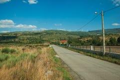 Straße, die durch hügelige Landschaft mit Bauernhöfen überschreitet lizenzfreie stockfotografie