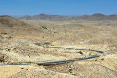 Straße, die durch Sahara-Wüste überschreitet Lizenzfreies Stockbild